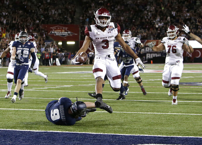 FILE - In this Dec. 29, 2017, file photo, New Mexico State running back Larry Rose III (3) leaps over Utah State linebacker David Woodward to score a touchdown in overtime and win the Arizona Bowl NCAA college football game in Tucson, Ariz. New Mexico State University has inked an agreement that opens the possibility of the Aggies making an appearance in the New Mexico Bowl or other postseason games owned by ESPN Events. (AP Photo/Rick Scuteri, File)