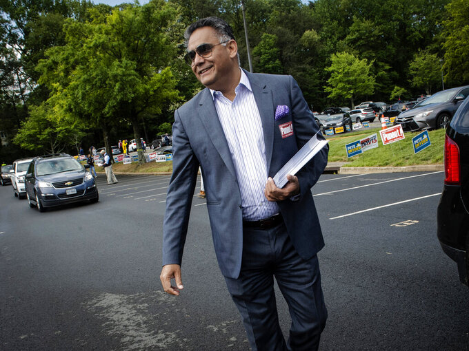Puneet Ahluwalia, candidate for Lt. Governor, works the line of cars during the Virginia GOP drive-thru primary to select candidates for the 2021 general election, Saturday, May 8, 2021, in Annandale, Va. (Bill O'Leary/The Washington Post via AP)