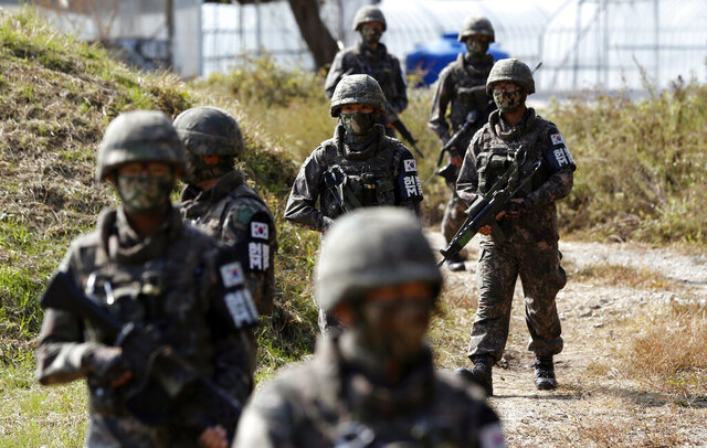 FILE- In this Oct. 13, 2015, file photo, South Korean Army soldiers patrol during the demonstration of search operation at a training field near the demilitarized zone (DMZ) in Cheorwon, South Korea. In the first such case in South Korea, military officials will determine next week whether to discharge a solider who recently undertook gender reassessment surgery, officials said Friday, Jan. 17, 2020. (AP Photo/Lee Jin-man, File)