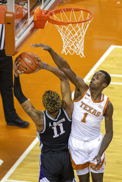 Kansas State forward Anftonio Gordon (11) drives against Texas guard Andrew Jones (1) in the first half of an NCAA college basketball game Saturday, Jan. 16, 2021, in Austin, Texas. (Ricardo B. Brazziell/Austin American-Statesman via AP)