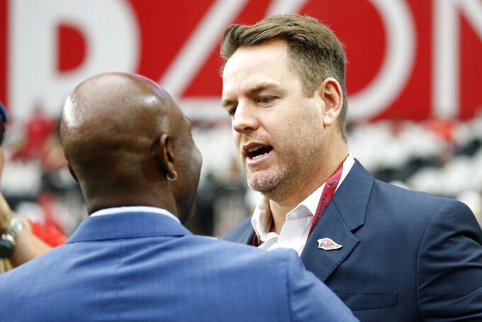 Former Arizona Cardinals quarterback Carson Palmer greets NFL Hall of Famer Jerry Rice prior to an NFL football game between the Seattle Seahawks and the Arizona Cardinals, Sunday, Sept. 29, 2019, in Glendale, Ariz. (AP Photo/Ross D. Franklin)