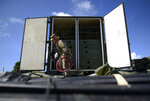 A member of the US army reserve works to set up up portable showers in a tent city for hundreds of people displaced by earthquakes in Guanica, Puerto Rico, Tuesday, Jan. 14, 2020. A 6.4 magnitude quake that toppled or damaged hundreds of homes in southwestern Puerto Rico is raising concerns about where displaced families will live, while the island still struggles to rebuild from Hurricane Maria two years ago. (AP Photo/Carlos Giusti)