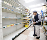A man who wanted to buy curing tape, stands in front of empty shelves at a home improvement center in Yokohama, near Tokyo Friday, Oct. 11, 2019. A typhoon was forecast to bring 2 feet of rain and damaging winds to the Tokyo area and central Japan's Pacific coast this weekend, and the government warned people Friday to stockpile and leave high-risk places before it's too dangerous. (Shohei Miyano/Kyodo News via AP)