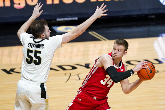 Wisconsin guard Brad Davison (34) looks to pass around Purdue guard Sasha Stefanovic (55) during the first half of an NCAA college basketball game in West Lafayette, Ind., Tuesday, March 2, 2021. (AP Photo/Michael Conroy)