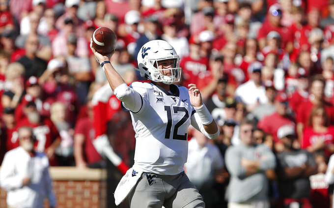 FILE - In this Oct. 19, 2019, file photo, West Virginia quarterback Austin Kendall (12) passes the ball against Oklahoma during the first half of an NCAA college football game in Norman, Okla. West Virginia has lost three straight games and will try to break a three-game losing streak Thursday night at Baylor.  (AP Photo/Alonzo Adams, File)