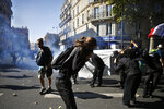 Protestors protect themselves from teargas during a climate demonstration, in Paris, Saturday, Sept. 21, 2019. Scuffles broke out in Paris between some violent activists and police which responded with tear gas at a march for climate gathering thousands of people in Paris. (AP Photo/Thibault Camus)