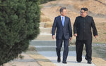 """FILE - In this April 27, 2018 file photo, North Korean leader Kim Jong Un, right, and South Korean President Moon Jae-in stroll together at the border village of Panmunjom in the Demilitarized Zone, South Korea. North Korea on Saturday, June 13, 2020 again bashed South Korea, telling its rival to stop """"nonsensical"""" talk about its denuclearization and vowing to expand its military capabilities. (Korea Summit Press Pool via AP, File)"""