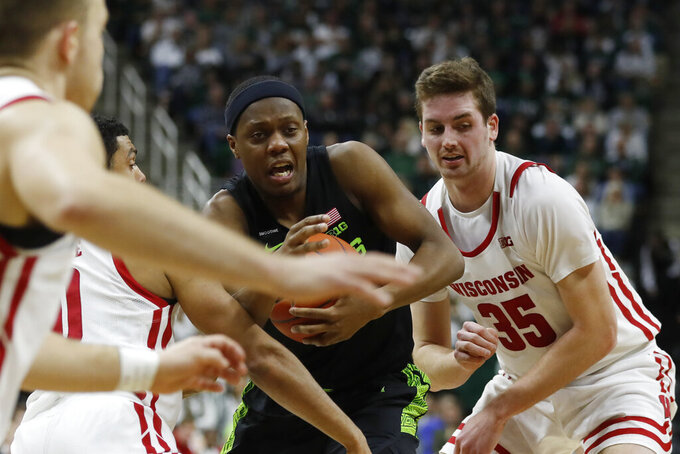Michigan State guard Cassius Winston, center, cuts through the defense of Wisconsin guard D'Mitrik Trice (0) and forward Nate Reuvers (35) during the second half of an NCAA college basketball game, Friday, Jan. 17, 2020, in East Lansing, Mich. (AP Photo/Carlos Osorio)