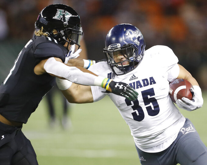 Nevada running back Toa Taua (35) tries to shove off Hawaii defensive back Jay Dominique (11) during the third quarter of an NCAA college football game Saturday, Oct. 20, 2018, in Honolulu. (AP Photo/Marco Garcia)