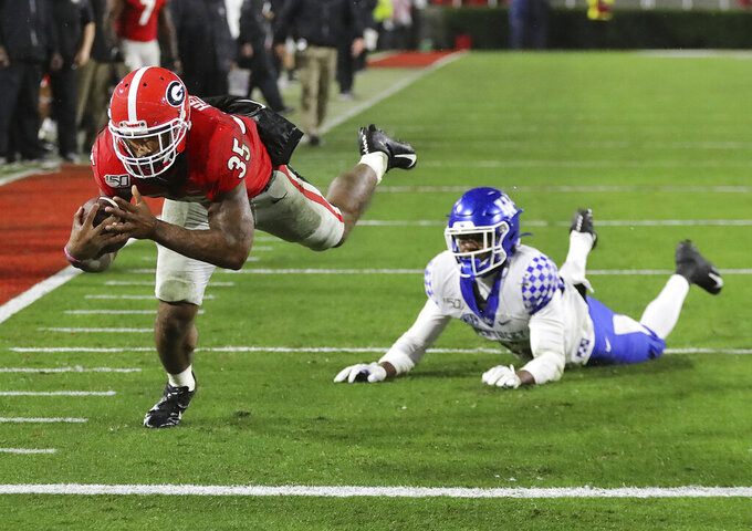 Georgia tailback Brian Herrien gets into the end zone past Kentucky defensive back Jamari Brown for a touchdown during the third quarter of an NCAA college football game Saturday, Oct. 19, 2019, in Athens, Ga. (Curtis Compton/Atlanta Journal Constitution via AP)