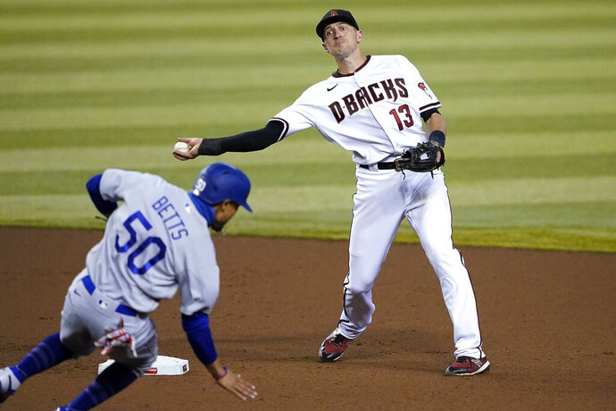 Arizona Diamondbacks' Nick Ahmed (13) forces out Los Angeles Dodgers' Mookie Betts (50) as he turns a double play on Corey Seager during the fourth inning of a baseball game, Thursday, Sept. 10, 2020, in Phoenix. (AP Photo/Matt York)