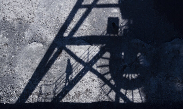 A man casts his shadow in the coal port of the Mehrum coal-fired power plant in the district of Peine in Hohenhameln, Germany, Wednesday, Jan. 15, 2020. Germany wants to gradually phase out the climate-damaging combustion of coal for electricity generation by 2038. ( Julian Stratenschulte/dpa via AP)
