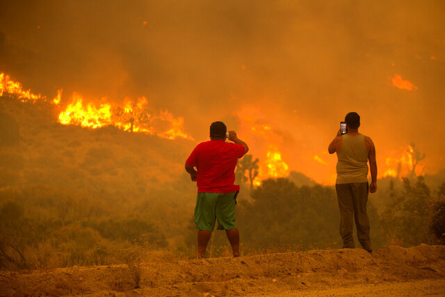 People take photos as the Bobcat Fire burns in Juniper Hill, Calif., Friday, Sept. 18, 2020. (AP Photo/Ringo H.W. Chiu)