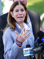 Linda Beigel Schulman, mother of Scott Beigel, a geography teacher and cross country coach who was killed during the Marjory Stoneman Douglas High School shooting last year, gestures as she speaks to members of the media during the one-year anniversary of the deadly shooting, Thursday, Feb. 14, 2019, in Parkland, Fla.  Thursday's anniversary was about remembering the 14 students and three staff members who died in the third high-profile mass shooting in Florida since 2016. (AP Photo/Wilfredo Lee)