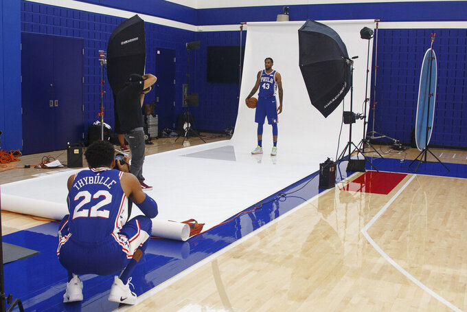 Philadelphia 76ers' Jonah Bolden, right, poses for a photograph as Matisse Thybulle, left, takes a photo of his own during media day at the NBA basketball team's practice facility, Monday, Sept. 30, 2019, in Camden, N.J. (AP Photo/Chris Szagola)