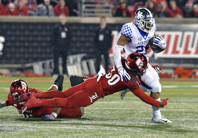 Kentucky running back Benny Snell Jr. (26) is grabbed by Louisville safety Khane Pass (30) during the first half of an NCAA college football game in Louisville, Ky., Saturday, Nov. 24, 2018. (AP Photo/Timothy D. Easley)