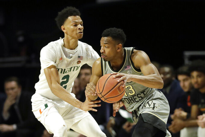 Wake Forest guard Andrien White (13) drives past Miami guard Isaiah Wong (2) during the first half of an NCAA college basketball game, Saturday, Feb. 15, 2020, in Coral Gables, Fla. (AP Photo/Wilfredo Lee)