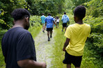 Students Giovanni Pierre, foreground left, and Aaron Overton, foreground right, walk behind camp educator Jamil Boykin, center, during a hike at Mass Audubon's Boston Nature Center and Wildlife Sanctuary, in the Mattapan neighborhood of Boston, Wednesday, June 23, 2021. Audubon Society chapters are grappling with how to address their namesake's legacy as the nation continues to reckon with its racist past. John James Audubon was a celebrated 19th century naturalist but also a slaveholder publicly opposed to abolition. (AP Photo/Steven Senne)