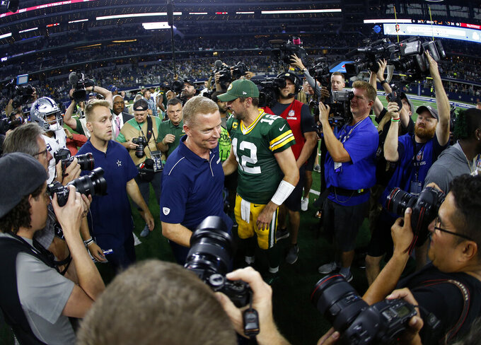Dallas Cowboys coach Jason Garrett, center left, and Green Bay Packers quarterback Aaron Rodgers (12) greet each other after an NFL football game in Arlington, Texas, Sunday, Oct. 6, 2019. (AP Photo/Ron Jenkins)