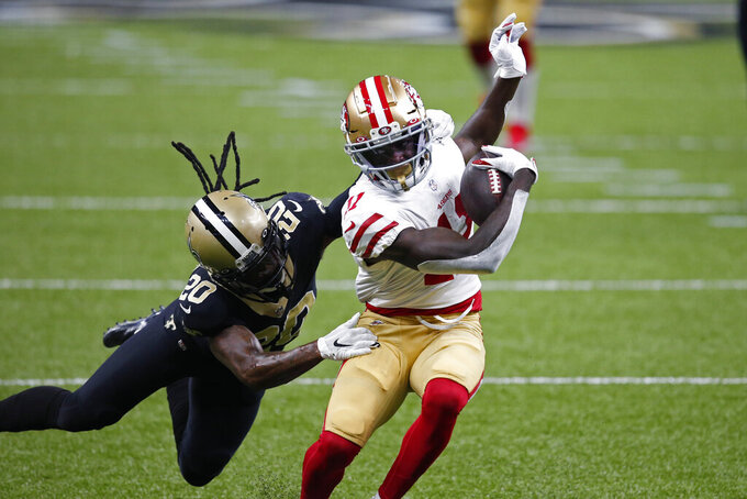 San Francisco 49ers wide receiver Brandon Aiyuk (11) tries to evade New Orleans Saints cornerback Janoris Jenkins (20) in the first half of an NFL football game in New Orleans, Sunday, Nov. 15, 2020. (AP Photo/Butch Dill)