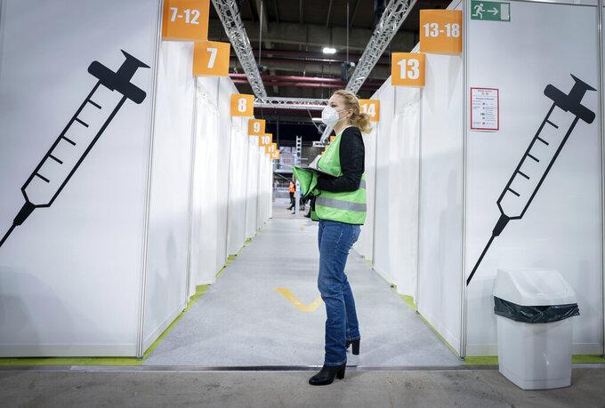 A volunteer stands inside the new open Erika-Hess-Eisstadion vaccine center in Berlin, Germany, Thursday,  Jan. 14, 2021. (Kay Nietfeld/Pool vis AP)
