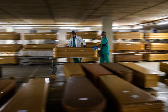 Workers move a coffin with the body of a victim of coronavirus as others coffins are stored waiting for burial or cremation at the Collserola morgue in Barcelona, Spain, Thursday, April 2, 2020. The new coronavirus causes mild or moderate symptoms for most people, but for some, especially older adults and people with existing health problems, it can cause more severe illness or death. (AP Photo/Emilio Morenatti)