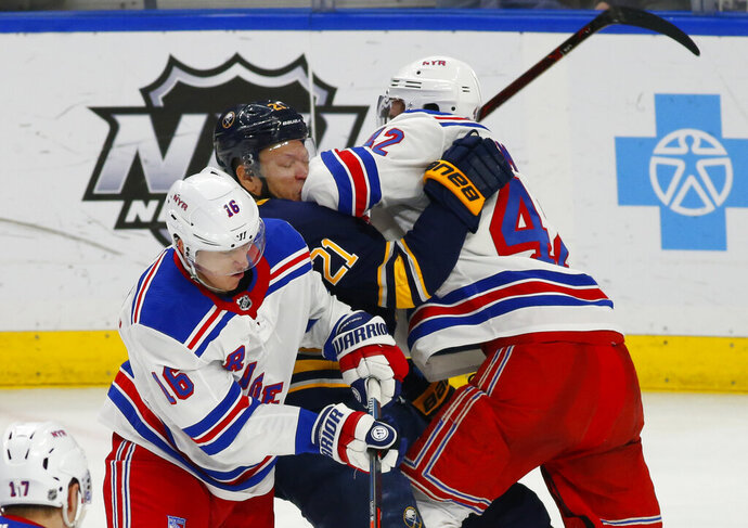 Buffalo Sabres forward Kyle Okposo (21) is hit by New York Rangers Ryan Strome (16) and Brendan Smith (42) during the third period of an NHL hockey game, Friday, Feb. 15, 2019, in Buffalo N.Y. (AP Photo/Jeffrey T. Barnes)