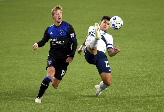 Vancouver Whitecaps forward Fredy Montero, right, kicks the ball away from San Jose Earthquakes midfielder Jackson Yueill, left, during the first half of an MLS soccer match in Portland, Ore., Saturday, Oct. 24, 2020. Vancouver won 2-1. (AP Photo/Steve Dykes)