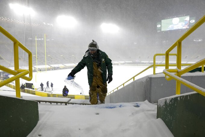 A worker applies salt as snow falls before an NFL football game between the Green Bay Packers and the Tennessee Titans at Lambeau Field Sunday, Dec. 27, 2020, in Green Bay, Wis. (AP Photo/Mike Roemer)