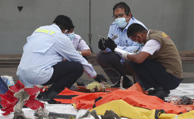 Indonesian National Transportation Safety Committee investigators inspect debris found in the waters around the location where a Sriwijaya Air passenger jet crashed, at the search and rescue command center at Tanjung Priok Port in Jakarta, Indonesia, Monday, Jan 18, 2021. (AP Photo/Achmad Ibrahim)