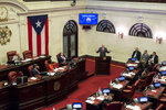 Puerto Rico Senate President Thomas Rivera Schatz, at the podium, gives his position against the confirmation of Pedro Pierluisi, currently the secretary of state, as new governor in San Juan, Puerto Rico, Monday, Aug. 5, 2019. Puerto Rico's Supreme Court on Monday agreed to rule on a lawsuit that the island's Senate filed in a bid to oust the veteran politician recently sworn in as the island's governor. (AP Photo/Dennis M. Rivera Pichardo)