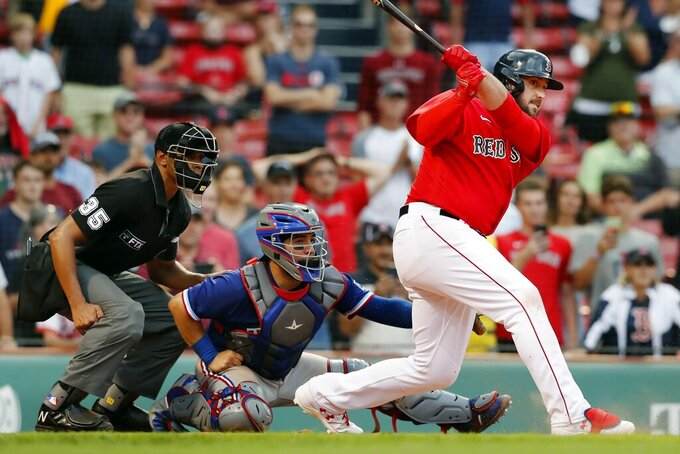CORRECTS TO JOSE TREVINO, NOT JONAH HEIM - Boston Red Sox's Travis Shaw, right, follows through on this walkoff grand slam in front of Texas Rangers' Jose Trevino during the 11th inning of a baseball game, Monday, Aug. 23, 2021, in Boston. (AP Photo/Michael Dwyer)