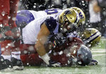 Washington State's Travell Harris, lower right, is tackled by Washington safety Taylor Rapp, upper left as snow flies during the first half of an NCAA college football game, Friday, Nov. 23, 2018, in Pullman, Wash. (AP Photo/Ted S. Warren)