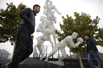 In this Friday, Oct. 11, 2019, photo, Chinese men walk by a sculpture depicting basketball players in Beijing. When Houston Rocket's general manager Daryl Morey tweeted last week in support of anti-government protests in Hong Kong, everything changed for NBA fans in China. A new chant flooded Chinese sports forums: