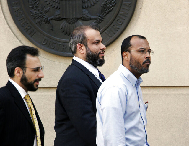 FILE - In this April 18, 2005 file photo, Ali Al-Tamimi, center, walks with two unidentified men, as he leaves the Albert V. Bryan Courthouse, in Alexandria, Va. A judge on Tuesday, Aug. 18, 2020 ordered Islamic scholar Ali Al-Tamimi, serving a life sentence for soliciting treason after the Sept. 11 attacks, be released from custody while he pursues his appeal. The order Tuesday grants release to Ali Al-Timimi in part because of concerns he is susceptible to the coronavirus and in part because of a recent Supreme Court case that could invalidate several counts on which he was convicted back in 2005.   (AP Photo/Manuel Balce Ceneta, File)