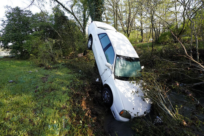 A car that was carried by floodwaters leans against a tree in a creek Sunday, March 28, 2021, in Nashville, Tenn. Heavy rain across Tennessee flooded homes and roads as a line of severe storms crossed the state. (AP Photo/Mark Humphrey)