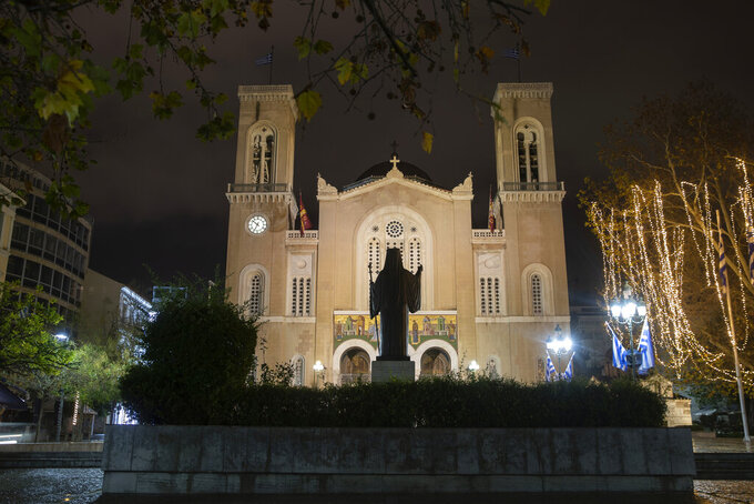 The statue of past Church leader Archbishop Damaskinos stands in front of the Athens Orthodox Cathedral, in Athens, on Monday Jan. 4, 2021. Greece's powerful Orthodox Church is rebelling against a government order to briefly close places of worship under a weeklong drive to tighten virus restrictions ahead of the planned reopening of schools. (AP Photo/Petros Giannakouris)