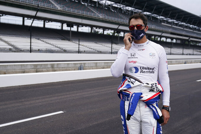 Graham Rahal makes a phone call during a practice session for the Indianapolis 500 auto race at Indianapolis Motor Speedway, Wednesday, Aug. 12, 2020, in Indianapolis. (AP Photo/Darron Cummings)