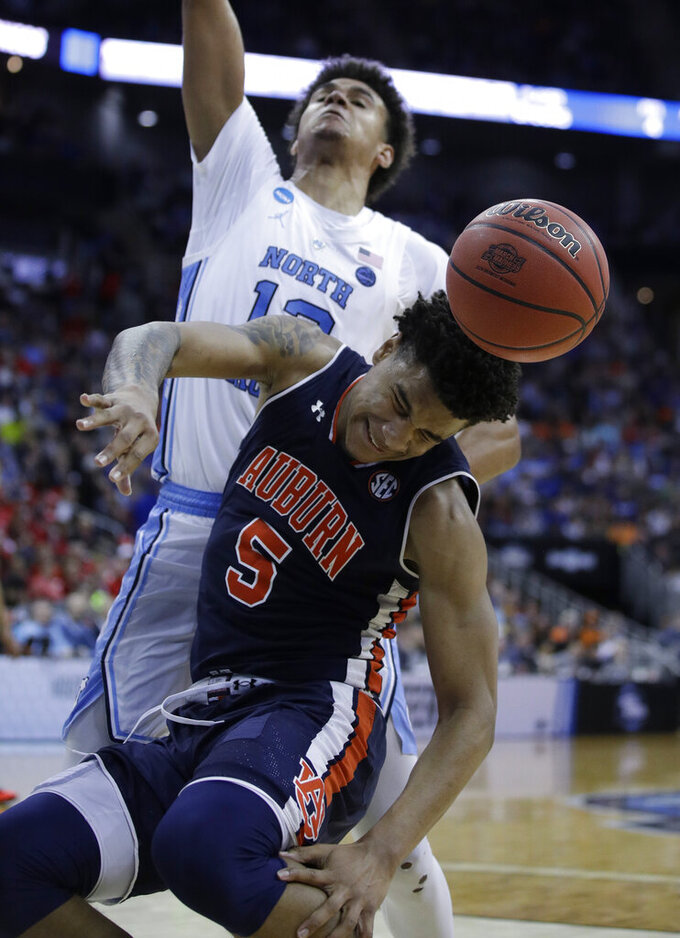 Auburn's Chuma Okeke (5) grabs his leg as he goes down heading to the basket past North Carolina's Cameron Johnson during the second half of a men's NCAA tournament college basketball Midwest Regional semifinal game Friday, March 29, 2019, in Kansas City, Mo. Okeke was injured on the play. (AP Photo/Charlie Riedel)