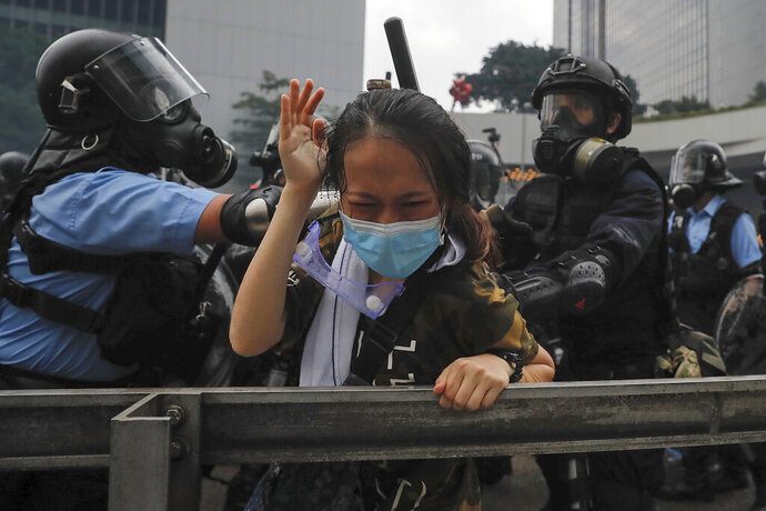 In this Wednesday, June 12, 2019, file photo, a protester reacts as she tackled by riot police during a massive demonstration outside the Legislative Council in Hong Kong. (AP Photo/Kin Cheung, File)