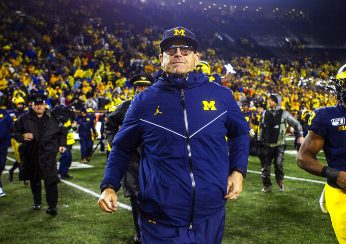 Michigan head coach Jim Harbaugh walks off the field at the end of an NCAA college football game against Notre Dame in Ann Arbor, Mich., Saturday, Oct. 26, 2019. Michigan won 45-14. (AP Photo/Tony Ding)