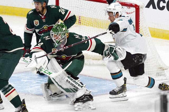 San Jose Sharks' Dylan Gambrell, right, tries to hold back Minnesota Wild goalie Kaapo Kahkonen in the third period of an NHL hockey game, Friday, Jan. 22, 2021, in St. Paul, Minn. (AP Photo/Jim Mone)
