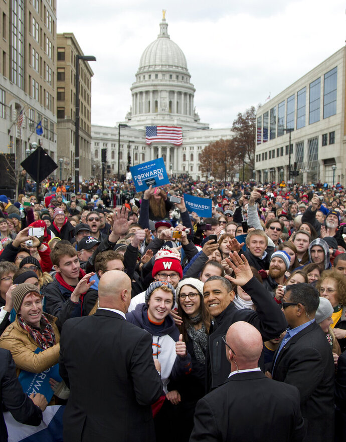 FILE - In this Nov. 5, 2012, file photo, the Wisconsin state capitol dome becomes a backdrop as President Barack Obama waves to photographers as he greets supporters at a campaign event in downtown Madison, Wis. Vice President Mike Pence is scheduled to give a speech Tuesday, Jan. 28, 2020, possibly the first visit by a sitting vice president or president inside Wisconsin's state Capitol building in its 103-year history , but Democratic Gov. Tony Evers won't be in his office just a few feet away when it happens. (AP Photo/Carolyn Kaster, File)