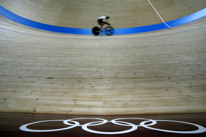 A rider rounds the track past Olympic Rings during a training session inside the Izu velodrome at the 2020 Summer Olympics, Sunday, Aug. 1, 2021, in Izu, Japan. (AP Photo/Christophe Ena)