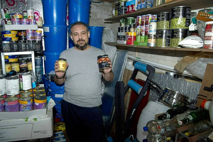 Melvin Burton holds up stored provisions in his garden shed in Littleport, Cambridgeshire, England, Friday March 1, 2019. For almost as long as Britain and the European Union have been wrangling over Brexit, Burton has been preparing for a bumpy landing. He's growing vegetables, drying fruit and buying in bulk. He reels off the cornucopia of cans filling his shed and the cupboard under his stairs: