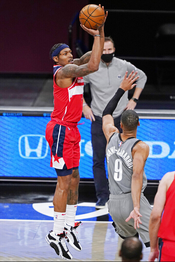 Washington Wizards head coach Scott Brooks looks on as guard Bradley Beal (3) shoots over Brooklyn Nets guard Timothe Luwawu-Cabarrot (9) during the second quarter of an NBA basketball game, Sunday, Jan. 3, 2021, in New York. (AP Photo/Kathy Willens)