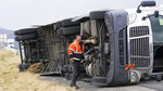 A semi rests in its side after after high winds toppled it on Interstate 15 Tuesday, Sept. 8, 2020, near Bountiful, Utah. Strong winds knocked out power in northern Utah, where temperatures dropped by 40 degrees. (AP Photo/Rick Bowmer)