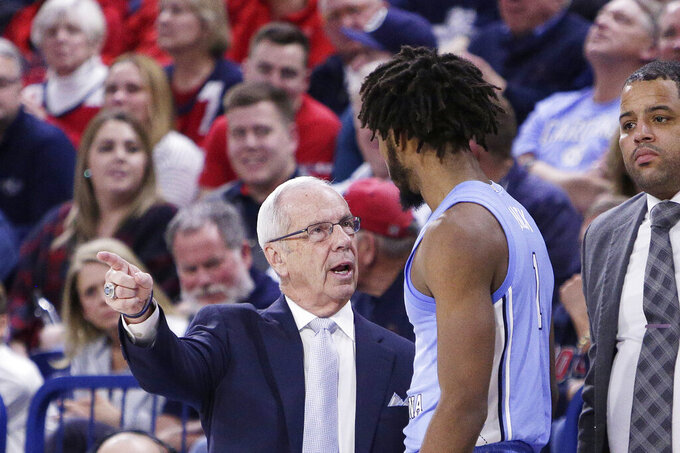 North Carolina head coach Roy Williams, left, speaks with guard Leaky Black (1) during the second half of an NCAA college basketball game in Spokane, Wash., Wednesday, Dec. 18, 2019. Gonzaga won 94-81. (AP Photo/Young Kwak)