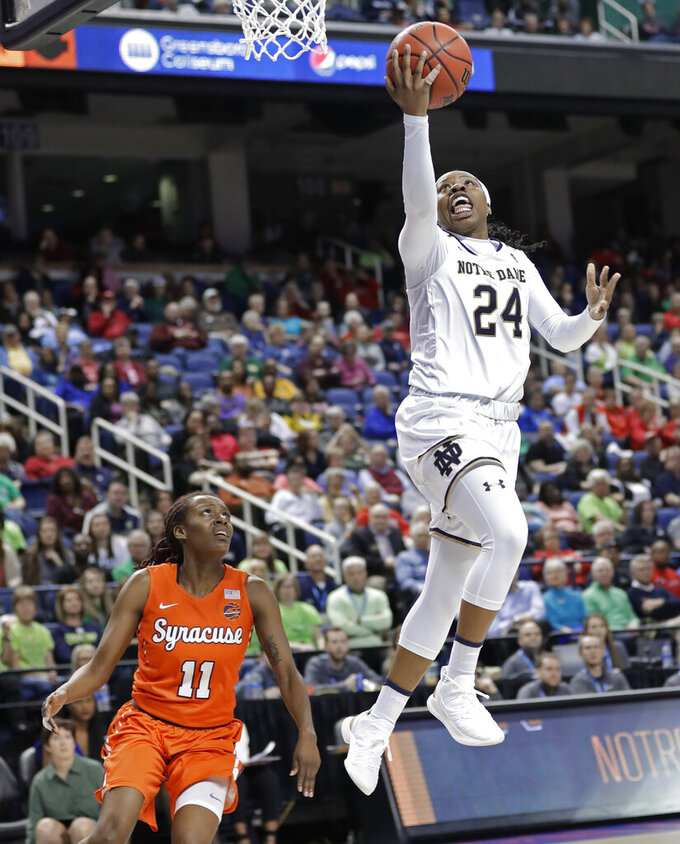 FILE- In this March 9, 2019, file photo Notre Dame's Arike Ogunbowale (24) drives to the basket past Syracuse's Gabrielle Cooper (11) during the second half of an NCAA college basketball game in the Atlantic Coast Conference tournament in Greensboro, N.C. The heroine of Notre Dame's national championship run last year, who won both Final Four and title games with dramatic, last-second shots, is ready for her last ride through the bracket, starting Saturday when the Fighting Irish takes on Bethune-Cookman in the first round. (AP Photo/Chuck Burton, File)