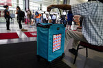 A poll worker hangs on the ballot box at a satellite election office at Temple University's Liacouras Center, Tuesday, Sept. 29, 2020, in Philadelphia. (AP Photo/Matt Slocum)